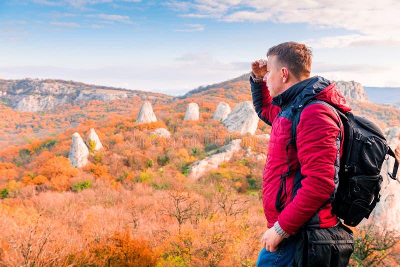 Facendo un'escursione nelle montagne, un viaggiatore che ammira l'autunno fotografia stock