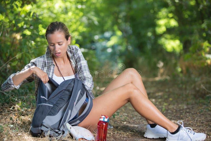 Facendo un'escursione ragazza che ha rottura che si siede nel pavimento della foresta immagini stock libere da diritti