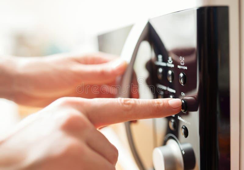 Facendo uso del forno a microonde, fine sulla foto fotografia stock libera da diritti