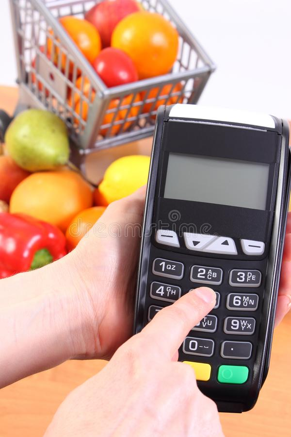 Facendo uso del terminale di pagamento, della frutta e delle verdure, pagamento cashless il concetto di compera fotografia stock