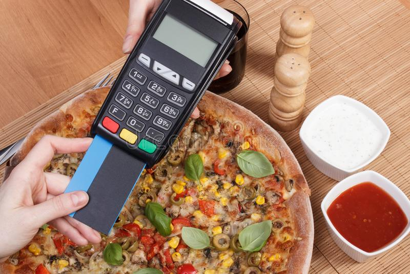 Facendo uso della carta di credito e del terminale di pagamento per il pagamento nel ristorante, concetto di finanza, pizza veget immagine stock
