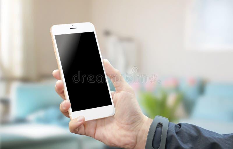 Facendo uso dello Smart Phone d'argento bianco nella sala Schermo in bianco del dispositivo mobile per il modello immagini stock libere da diritti