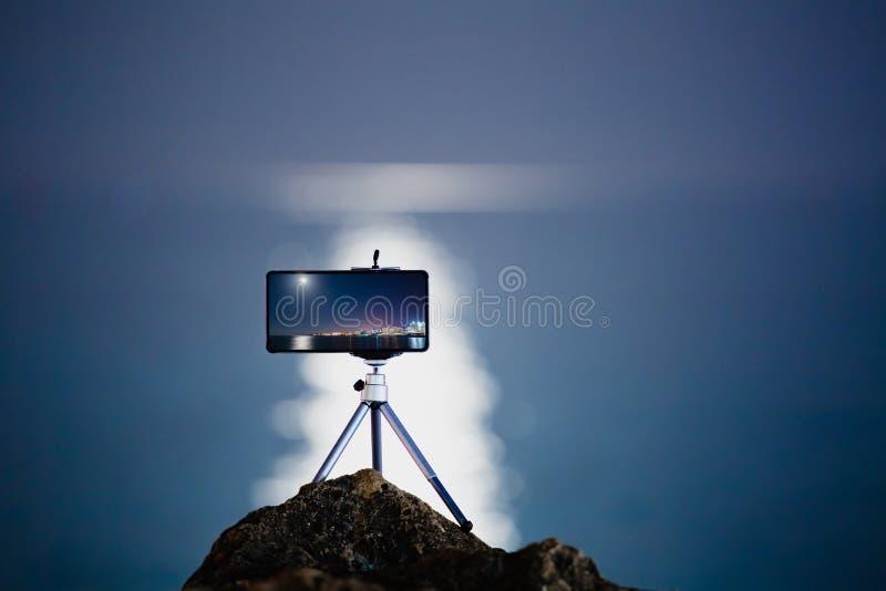 Facendo uso dello smartphone sul treppiede a fare la foto con la bella strada della luna immagine stock