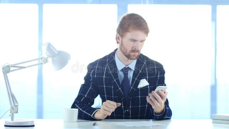 Facendo uso di Smartphone per la lettura invia con la posta elettronica i messaggi di nad, equipaggiano con i capelli rossi fotografie stock