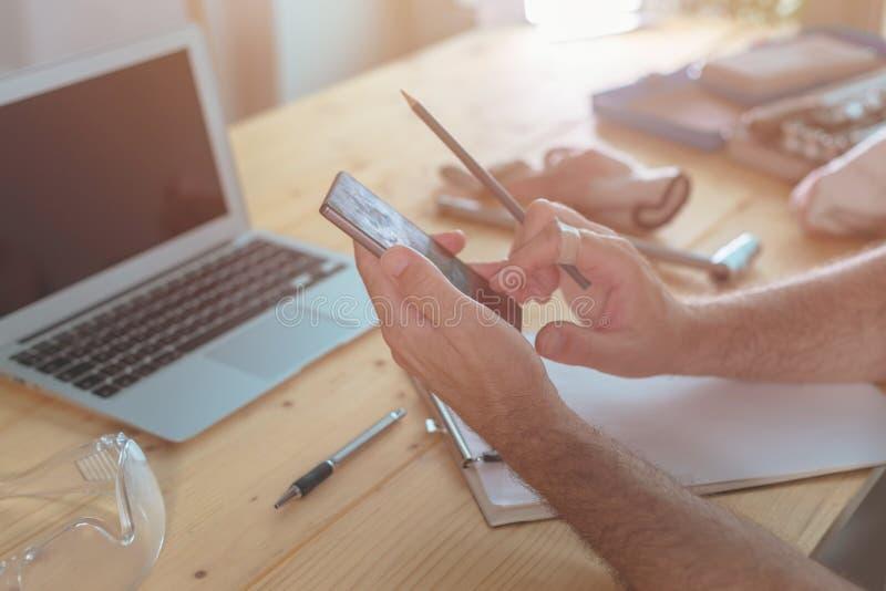 Facendo uso di tecnologia moderna nell'officina di piccola impresa immagini stock libere da diritti