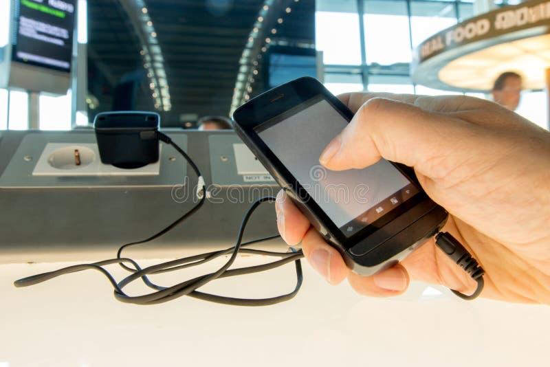 Facendo uso di un telefono cellulare mentre caricando la batteria immagini stock libere da diritti