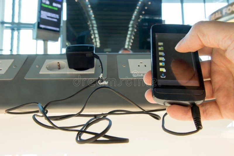 Facendo uso di un telefono mentre caricando la batteria all'aeroporto immagine stock