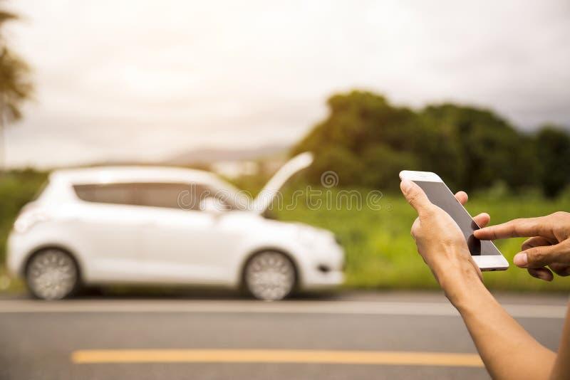 Facendo uso di una chiamata di telefono cellulare un meccanico di automobile perché l'automobile era rotta fotografia stock libera da diritti