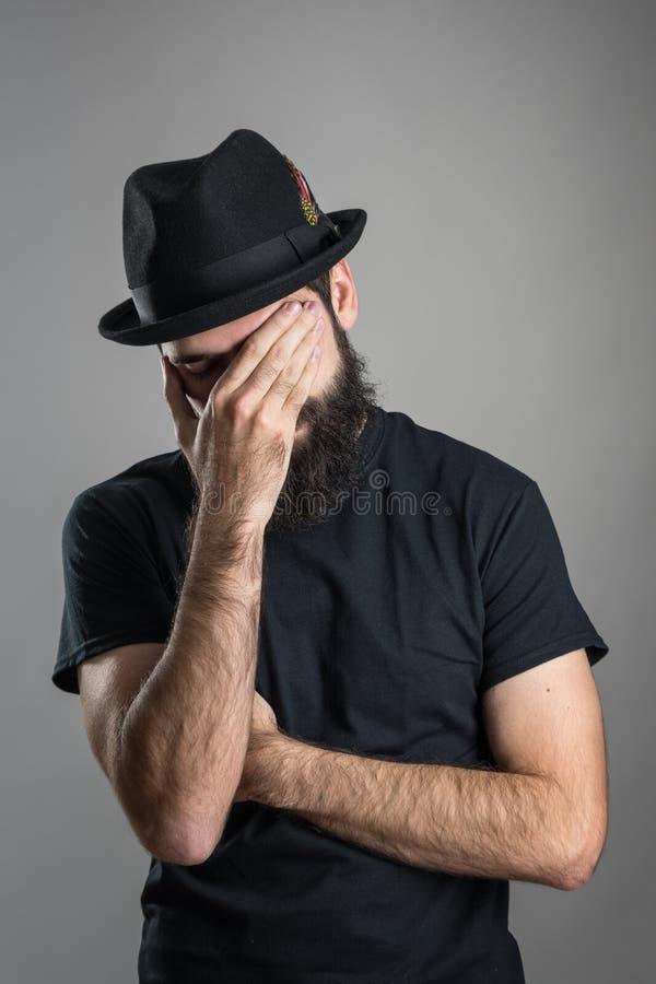Facepalm van gebaarde hipster die zwarte hoed en t-shirt dragen stock foto