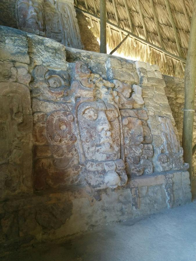 Faces carved in stone on two levels in Mayan ruins. Faces and symbols carved in stone on two levels under a protective thatched roof in Kohunlich Mayan ruins, in royalty free stock image