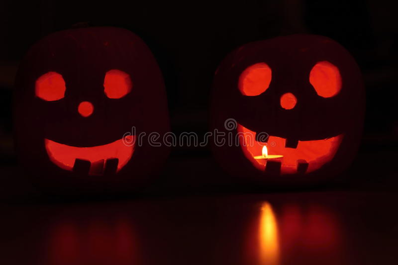 Faces of the Halloween pumpkins in the dark. Candle lit faces of the Halloween pumpkins in the dark royalty free stock photo