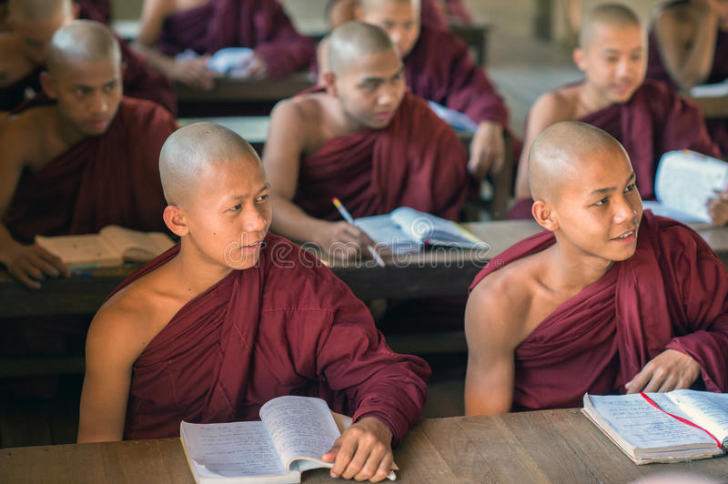 Faces of Myanmar. Bagan, Myanmar - February 8, 2014: Young Burmese novice monks study books. Buddhists in Myanmar belong mainly to the Theravada tradition royalty free stock photography