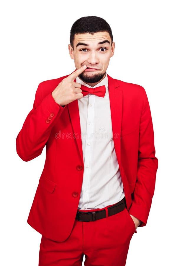 Facet coś wtykającego w jego zębach śmieszny mężczyzna w czerwonym kostiumu pokazuje palec w jego usta obraz stock