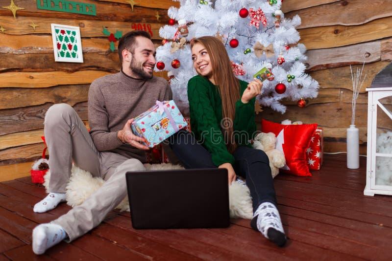 Facet daje prezentowi dziewczyny obsiadanie na dywaniku na tle choinka zdjęcia royalty free