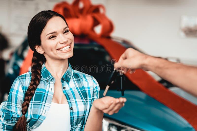 Facet Daje Samochodowemu kluczowi dziewczyna odizolowywający nad biel pojęcie prezent obraz royalty free
