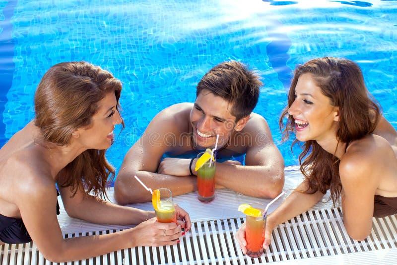 Facet flirtuje z dwa kobietami przy pływackim basenem obraz royalty free