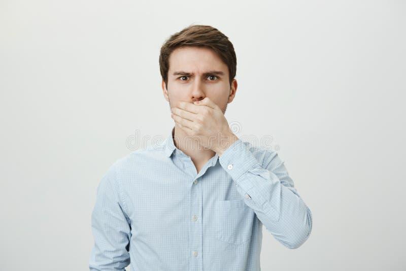 Facet iść rzucać up Zmartwiony szokujący caucasian samiec modela nakrywkowy usta z palmą, patrzeje nerwowy podczas gdy próbujący obrazy stock