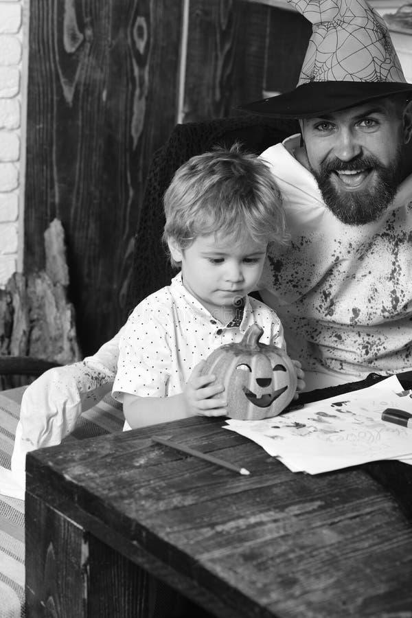 Facet i chłopiec na drewnianym tle Witcher i mały magik dostajemy gotowymi dla Halloween zdjęcia royalty free