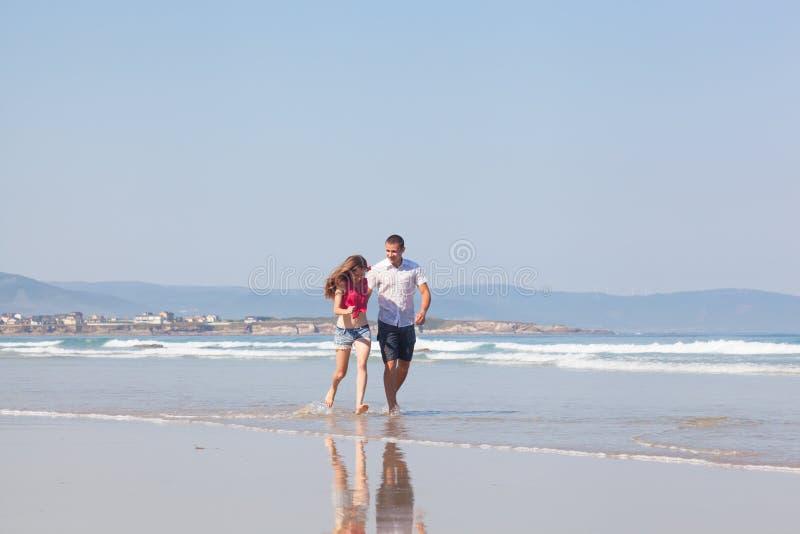 Facet i dziewczyna bieg na plaży zdjęcia royalty free