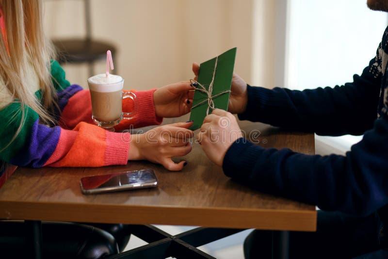 Facet i dziewczyna pijemy kawę w kawiarni mężczyzna dać dziewczynie zielonej kopercie z niespodzianką kobieta jesteśmy bardzo szc obraz royalty free