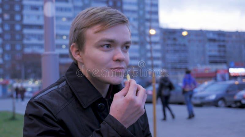 Facet je dłoniaki kartoflanych na ulicie na ławce, Mężczyzna łasowania francuza dłoniaki, smażąca grula, szczerbią się, niezdrowy obraz stock
