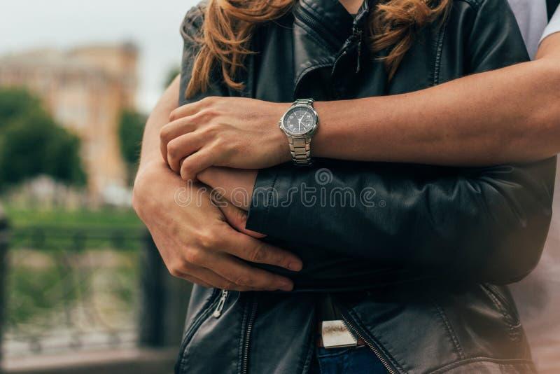 facet jest behind i ściska dziewczyny, wręcza wpólnie na ręce facet jest ubranym zegarek data samiec wręcza, wręcza, zakończenie, obrazy stock