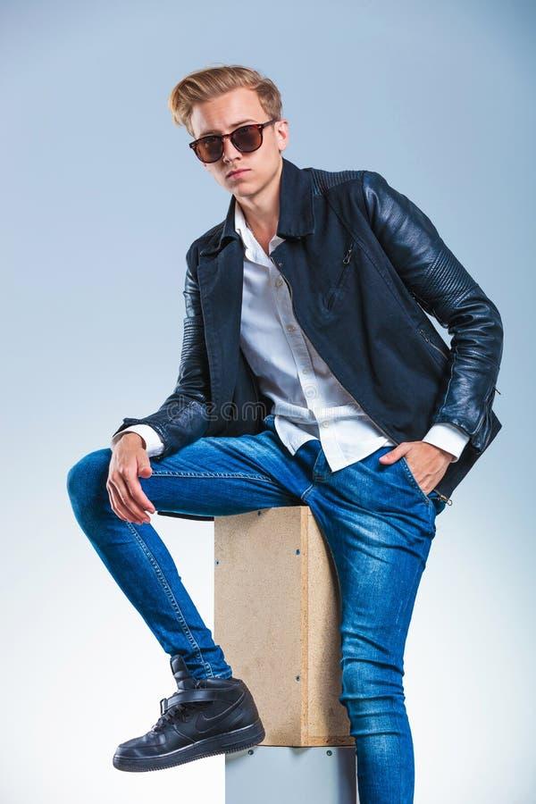 Facet jest ubranym okulary przeciwsłonecznych i skórzaną kurtkę podczas gdy mieć jego wręczać fotografia royalty free