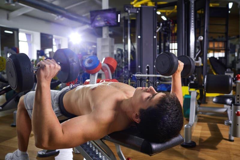 Facet kłama robić z dumbbells ćwiczy w gym zdjęcie stock