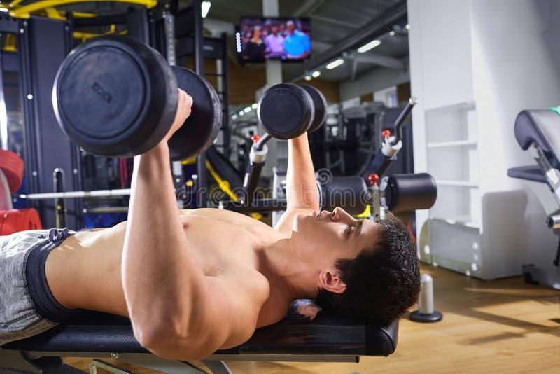Facet kłama robić z dumbbells ćwiczy w gym zdjęcia stock