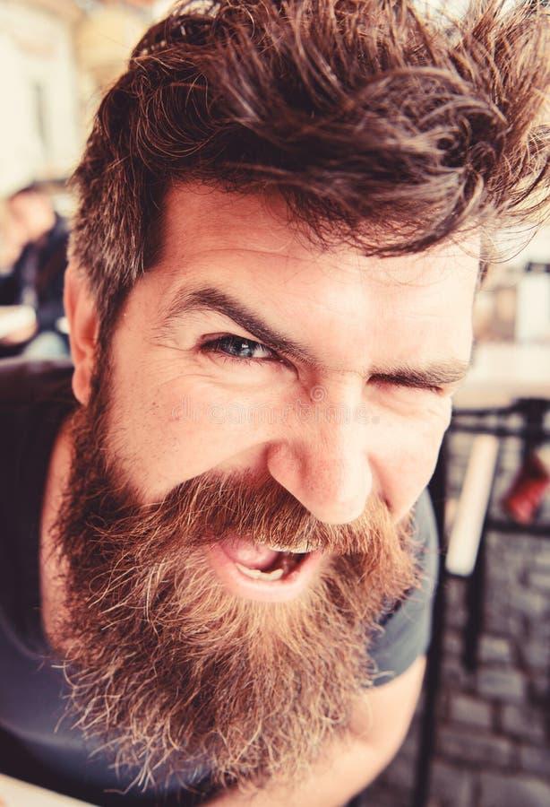 Facet ma odpoczynek przy kawiarnia tarasem, zamyka up Mężczyzna z brodą i wąsy w dobrym nastroju podczas gdy relaksujący przy kaw fotografia stock