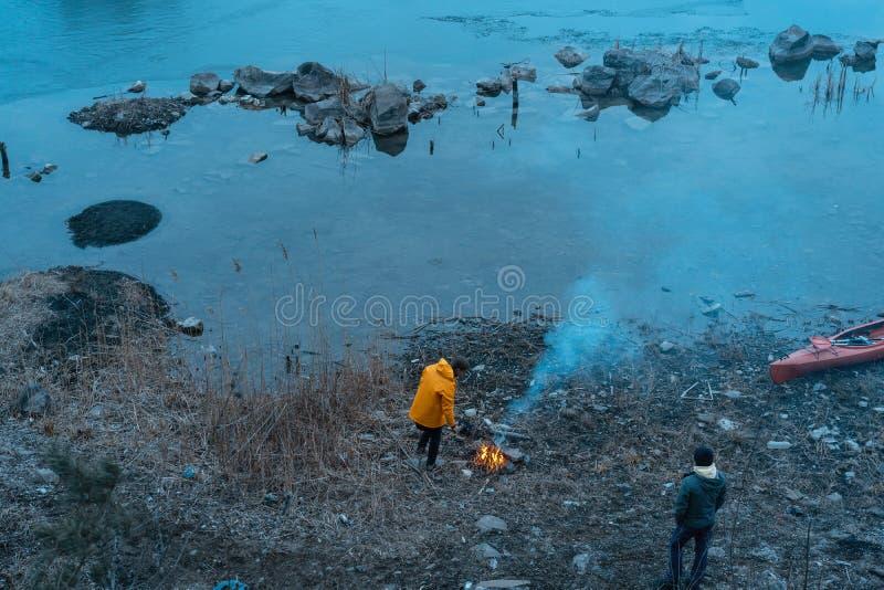 Facet na jeziorze robi ogieniowi zdjęcie royalty free