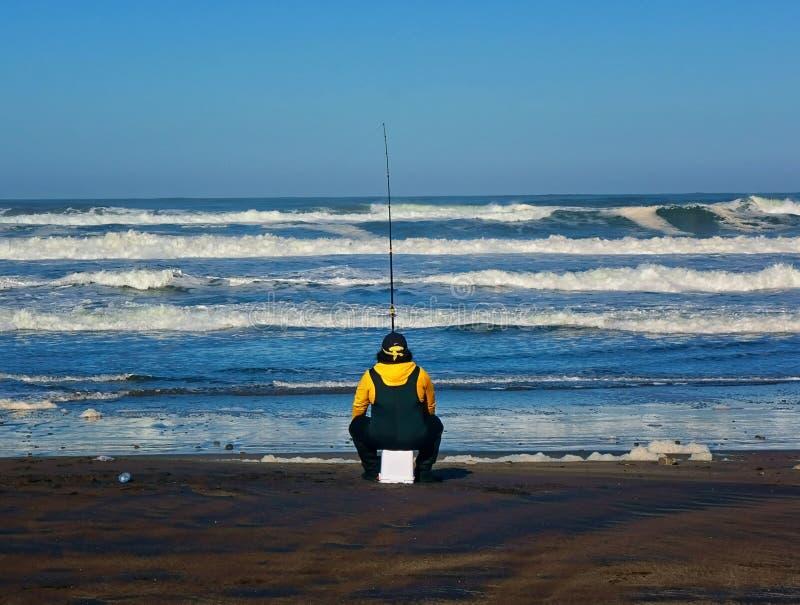 Facet na ocean plaży w San Fransisco robi niektóre kipiel połowowi podczas gdy siedzący na do góry nogami wiadrze obrazy royalty free