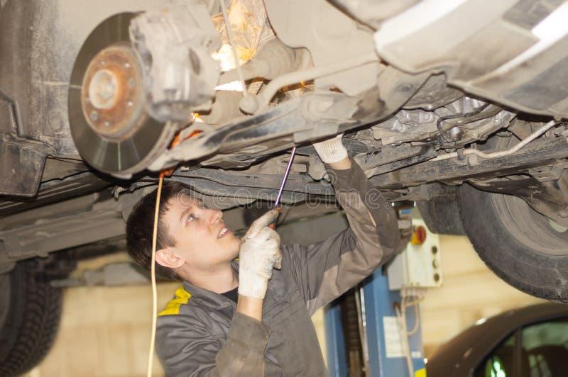 Facet naprawia samochód na dźwignięciu zdjęcia royalty free