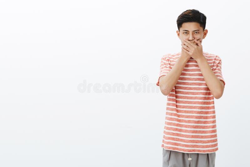 Facet nie w nastroju mówić Portret przyglądający intensywny młody azjatykci nastolatek w pasiastej koszulki naciskowych palmach obrazy royalty free