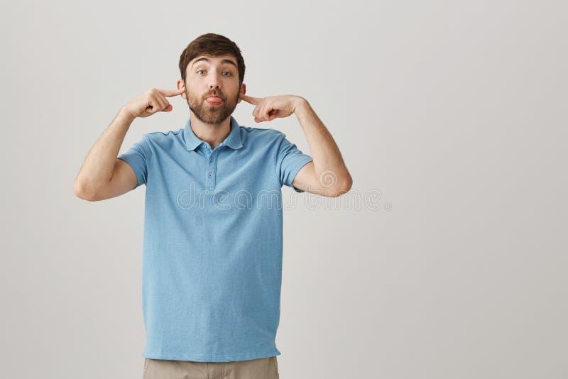 Facet no iść słuchać wymówki Portret beztroskiego atrakcyjnego brodatego faceta nakrywkowi ucho z palcami wskazującymi i fotografia royalty free