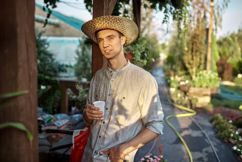 Facet ogrodniczka w słomianym kapeluszu stoi z plastikowym szkłem w jego ręce obok drewnianej werandy w cudownej pepinierze obraz stock