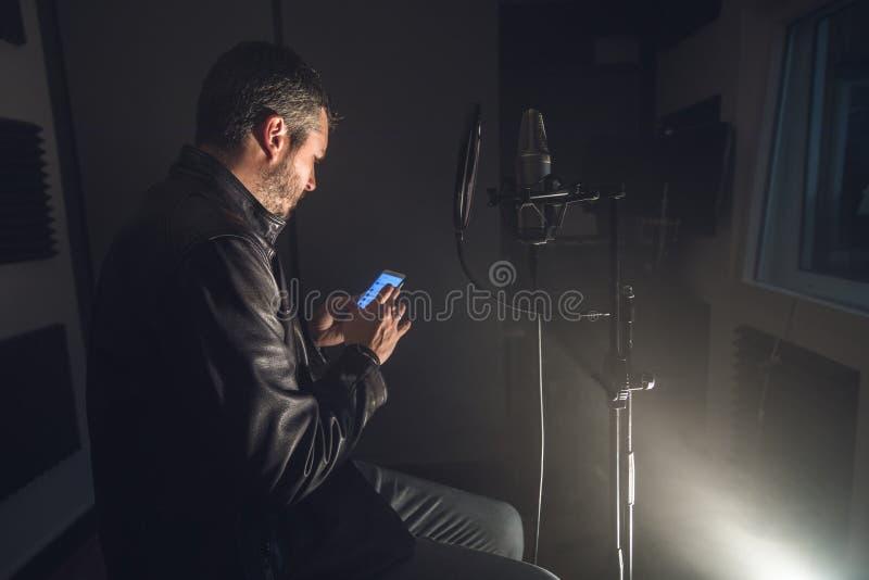 Facet patrzeje telefon komórkowego w muzycznym studiu fotografia royalty free