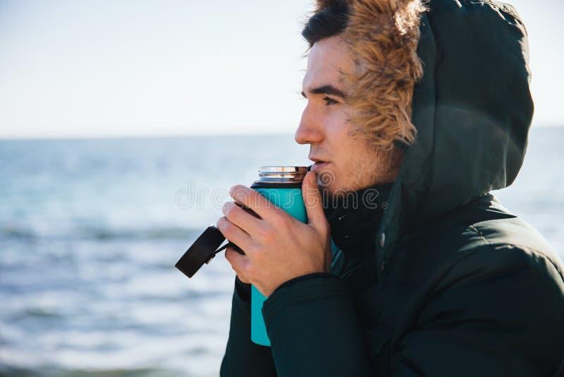Facet pije herbaty od termosu morzem obraz royalty free