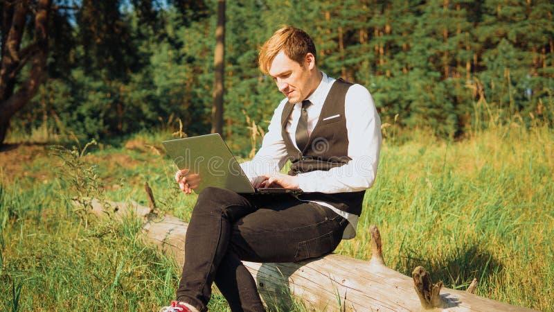 Facet pracuje przy komputerem w naturze na Pogodnym jasnym dniu Dla laptopu na ulicie pojęcie pracować freel, dokąd chcę obraz royalty free