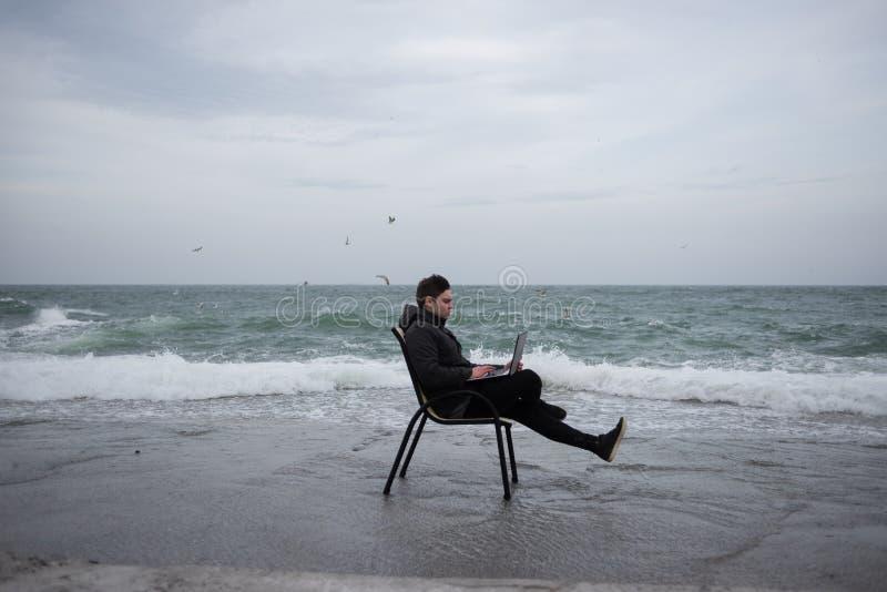 Facet pracuje w komputerze na seashore obrazy stock