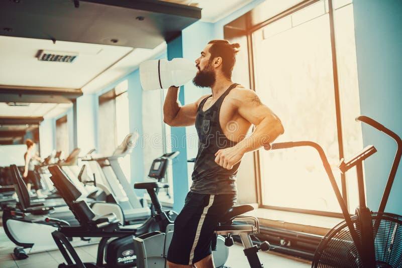 Facet relaksuje po treningu, chwyta i napoju wody od dużej butelki w gym zdjęcie stock