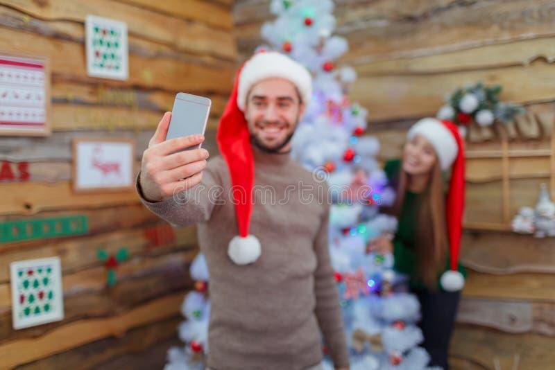 Facet robi selfie na tle dziewczyna przy choinką w pokoju z obrazkami obraz royalty free