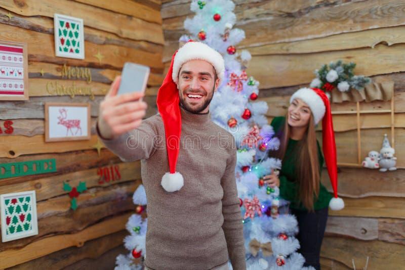 Facet robi selfie w tle z dziewczyną i drzewem w pokoju fotografia royalty free
