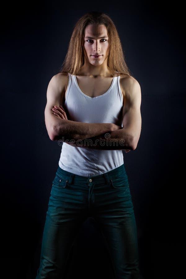 Facet samiec model z długie włosy pozować w studiu na czarnym tle, białej koszulka i cajgi obraz royalty free
