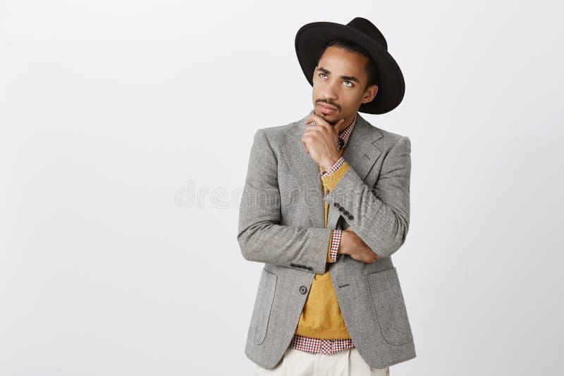 Facet skupiający się na myślach, robi trudnej decyzi Skoncentrowany poważny ciemnoskóry męski freelancer w czarnym kapeluszu i obraz royalty free