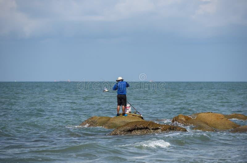 Facet spokojnego moment sam, łowiący na rockowej wyspie, Pattaya obrazy stock