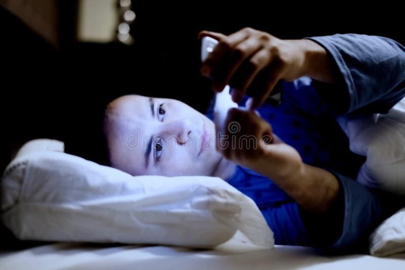 Facet używa jego telefon komórkowego w łóżku zdjęcie royalty free