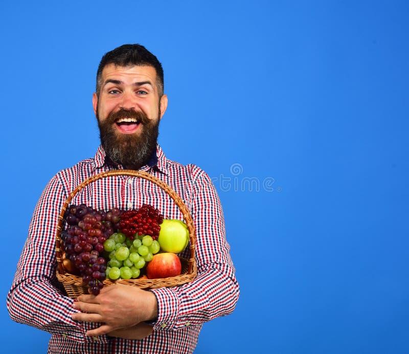 Facet Uprawia ziemię pojęcie i uprawia ogródek trzyma jego żniwo Rolnik z rozochoconą twarzą przedstawia jabłka, winogrona i cran fotografia royalty free