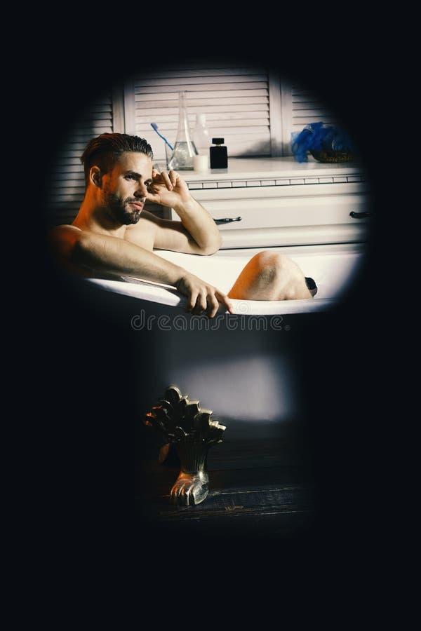 Facet w łazience z toiletries na tle Płeć i relaksu pojęcie Mężczyzna z brodą i marzycielską twarzą Macho obsiadanie obraz stock