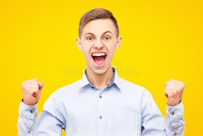 Facet w błękitnej koszula raduje się zwycięstwo odizolowywającego na żółtym tle, podnosić ręki w górę obraz royalty free